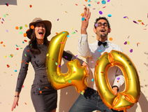 Cheerful couple celebrates a forty years birthday with big golden balloons and colorful little pieces of paper in the air Royalty Free Stock Photos
