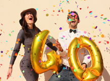 Cheerful couple celebrates a forty years birthday with big golden balloons and colorful little pieces of paper in the air Stock Photo