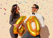 Cheerful couple celebrates a forty years birthday with big golden balloons and colorful little pieces of paper in the air Royalty Free Stock Images