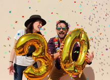 Cheerful couple celebrates a thirty years birthday with big golden balloons. And colorful little pieces of paper in the air royalty free stock photos