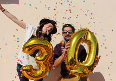 Cheerful couple celebrates a thirty years birthday with big golden balloons Stock Image
