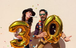Cheerful couple celebrates a thirty years birthday with big golden balloons. And colorful little pieces of paper in the air royalty free stock photography