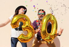 Cheerful couple celebrates a thirty years birthday with big golden balloons Stock Photography