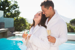Cheerful couple with champagne flutes by swimming pool Stock Photo