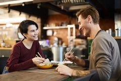 Cheerful Couple in Chinese Food Restaurant. Side view portrait of happy young couple enjoying Asian food in restaurant, copy space stock photos