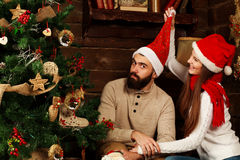 Cheerful couple in Christmas hats having fun in country house Stock Image