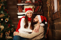 Cheerful couple in Christmas hats having fun in country house Royalty Free Stock Photos