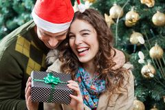 Cheerful Couple With Christmas Present In Store. Cheerful young couple with present against Christmas tree in store Royalty Free Stock Images