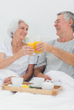 Cheerful couple clinking their orange juice glasses Stock Photos