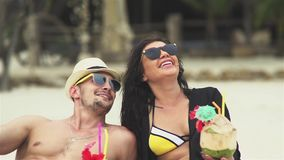 Cheerful Couple With Coconut Lying On The Beach. Slow motion portrait of a cheerful couple with coconut cocktails lying on the beach and relaxing stock footage