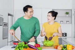 Cheerful couple cooking at home. Photo of two cheerful Asian couple cooking in the kitchen while looking to each other and laughing together Royalty Free Stock Image