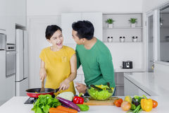 Cheerful couple cooking in kitchen Royalty Free Stock Photo