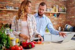 Cheerful couple cooking on modern kitchen Royalty Free Stock Photos