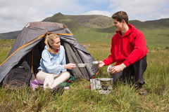 Cheerful couple cooking outdoors on camping trip Stock Photography