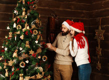 Cheerful couple decorates a Christmas tree in country house Stock Images