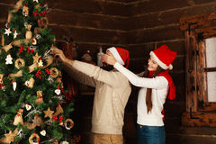 Cheerful couple decorates a Christmas tree in country house Royalty Free Stock Photography