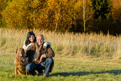 Cheerful couple with dog in autumn countryside stock photos