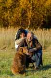 Cheerful couple with dog in autumn countryside royalty free stock images