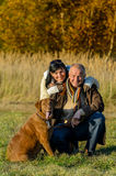 Cheerful couple with dog in autumn park Stock Photo