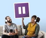 Interracial couple listening to music and holding a pause button royalty free stock images