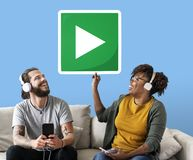 Interracial couple listening to music and holding a play button royalty free stock photo