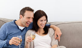 Cheerful couple drinking champagne on the sofa Stock Photo