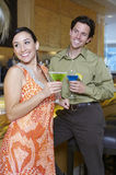 Cheerful Couple Drinking Martinis Stock Images