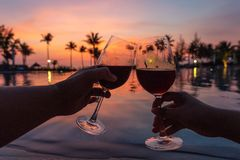 Cheerful couple drinking red wine in luxury resort at sunset royalty free stock photos