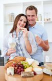 Cheerful couple drinking white wine. And eating cheese in the kitchen Stock Photo