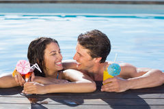 Cheerful couple with drinks in swimming pool Royalty Free Stock Photo