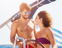 Cheerful couple driving sailboat Royalty Free Stock Photo