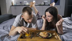 Cheerful couple eating breakfast pancakes in bed. Front view of young cheerful happy couple lying in bed together in the morning, eating pancakes and drinking stock video footage