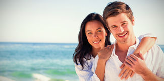 Cheerful couple embracing on the beach Stock Images
