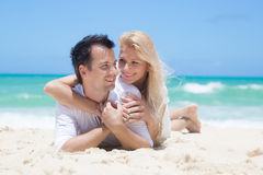 Cheerful couple embracing and lying on the beach o Stock Images