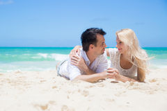 Cheerful couple embracing and lying on the beach o Stock Photo