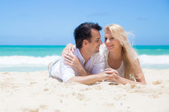 Cheerful couple embracing and lying on the beach on a sunny day Stock Photography