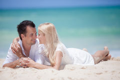 Cheerful couple embracing and lying on the beach on a sunny day Royalty Free Stock Photo
