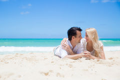 Cheerful couple embracing and lying on the beach on a sunny day Royalty Free Stock Image