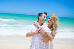 Cheerful couple embracing and posing on the beach  Stock Images