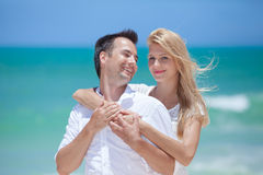 Cheerful couple embracing and posing on the beach  Royalty Free Stock Photos