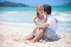 Cheerful couple embracing and posing on the beach  Royalty Free Stock Image