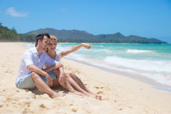 Cheerful couple embracing and posing on the beach  Stock Image