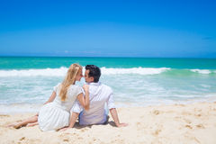 Cheerful couple embracing and posing on the beach  Royalty Free Stock Images