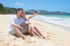 Cheerful couple embracing and posing on the beach  Stock Photography