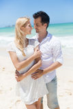 Cheerful couple embracing and posing on the beach on a sunny day Royalty Free Stock Photos