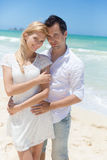 Cheerful couple embracing and posing on the beach on a sunny day Royalty Free Stock Photography