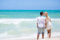 Cheerful couple embracing and posing on the beach on a sunny day Stock Image