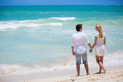 Cheerful couple embracing and posing on the beach on a sunny day Royalty Free Stock Image