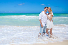 Cheerful couple embracing and posing on the beach on a sunny day Royalty Free Stock Images