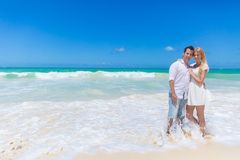 Cheerful couple embracing and posing on the beach on a sunny day Stock Photo